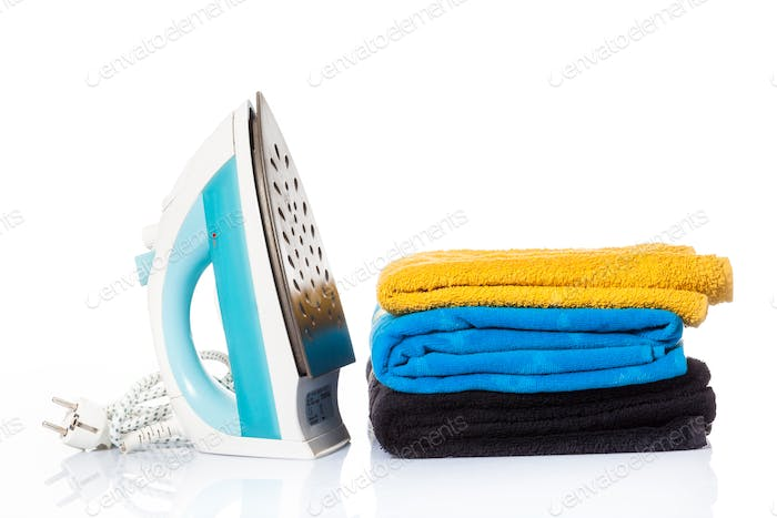 Electric iron and pile of clothes. electric iron isolated on whi