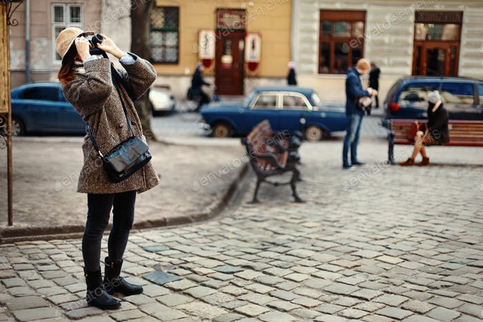 Happy and stylish hipster woman taking photo with film photo camera