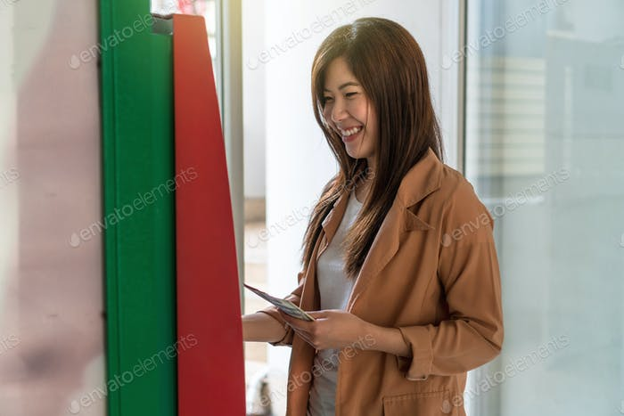Happy asian young woman holding the dollar money with smiling action after withdrawed cash