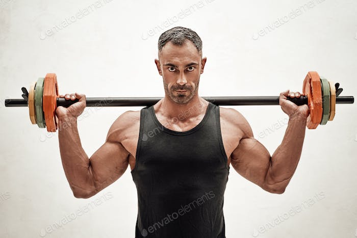 Close-up photo of a sportsman, flexing with a barbell in a bright studio