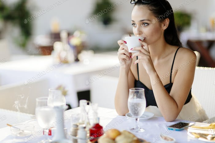 Beautiful woman drinking coffee in restaurant