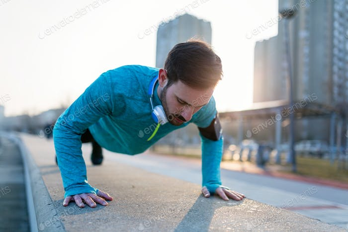 Young handsome man doing push ups outdoors