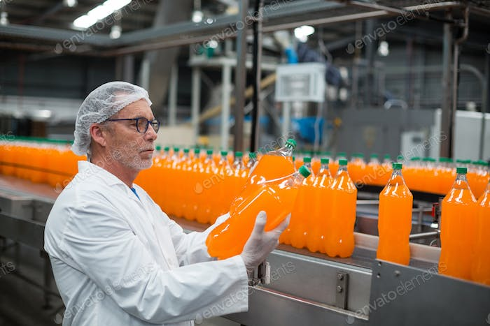 Factory engineer examining a bottle of juice