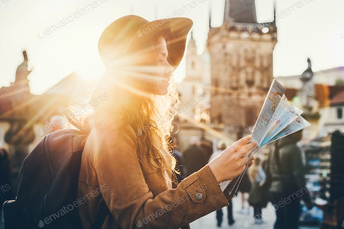 Girl with backpack looking at map. Girl visiting the sights Praha in holiday. Sun flare.