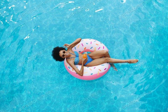 Sexy Afroamerikaner Frau mit Sommergetränk entspannen auf aufblasbaren Ring am Schwimmbad, Overhead
