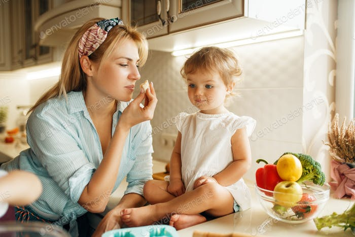 Young mother and kid tastes fresh chocolate pastry