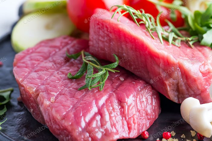 Raw beef steak on the bone with fresh vegetables in a grill pan close-up