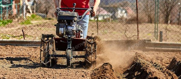 Gardener cultivate ground soil with tiller tractor or rototiller, cutivator