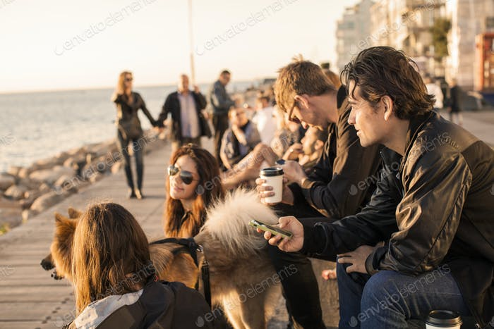 Friends with dog spending leisure time by sea