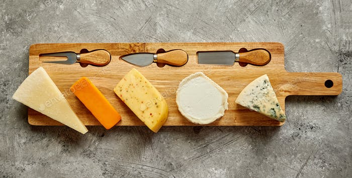 Assortment of various kinds of cheeses served on wooden board with fork and knives
