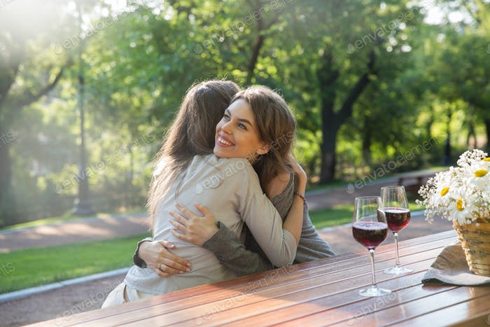 Happy young two women sitting outdoors in park drinking wine