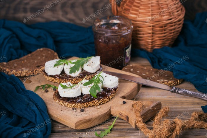 Bruschetta with fig jam, goat cheese and rucola on wooden plate