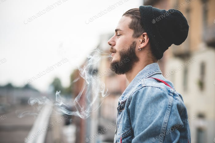young handsome bearded hipster man smoking cigarette