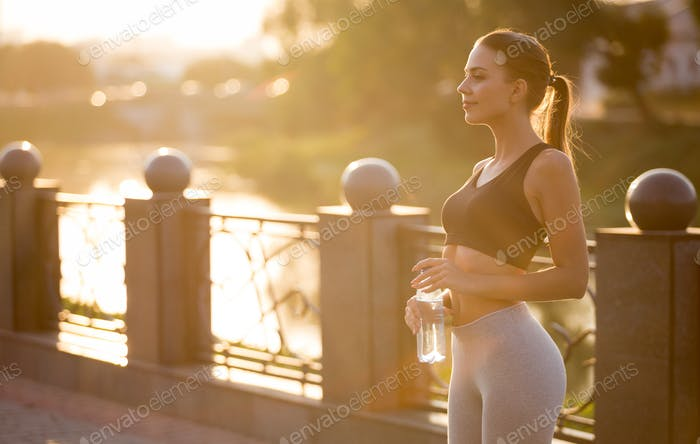 Young millennial woman enjoying sunrise in park after training