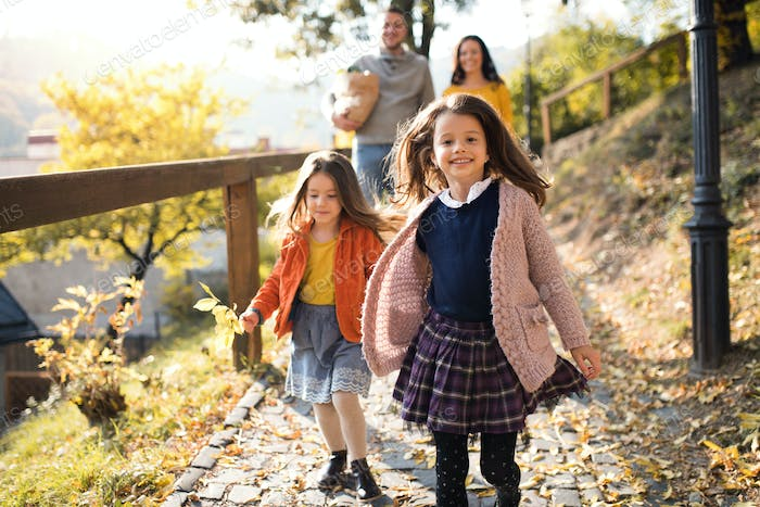 Two girls with unrecognizable parents in the background walking in park in autumn