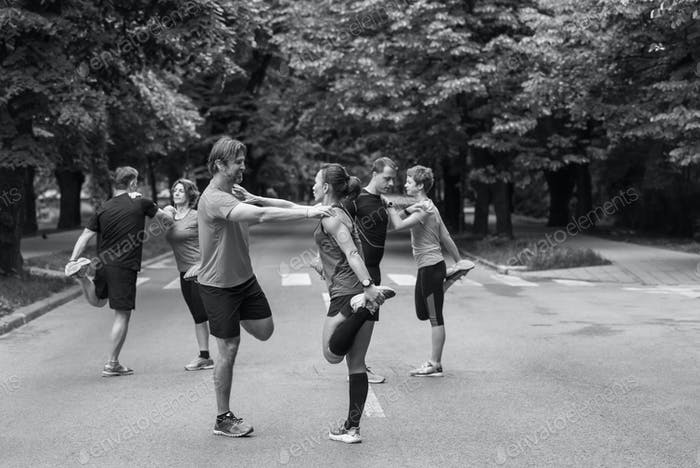 runners team warming up and stretching before morning training