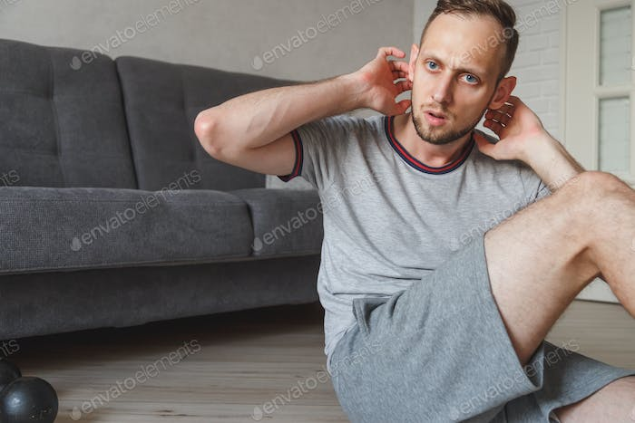 Caucasian young bearded man doing abdominals exercises near the couch at home