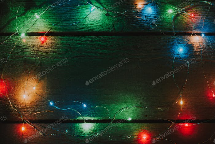Christmas tree lights decoration on bright wooden background with creative copy space.