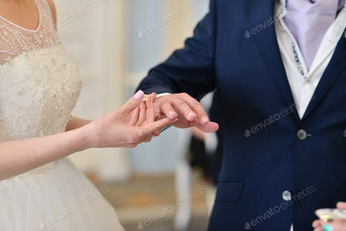 Beauty bride and handsome groom are wearing rings each other