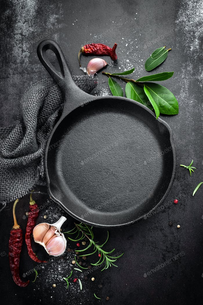 Gusseisen Pfanne und Gewürze auf schwarzem Metall kulinarischen Hintergrund, Blick von oben