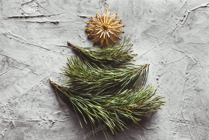 Christmas tree made from pine leaves and straw toys. on a gray concrete background
