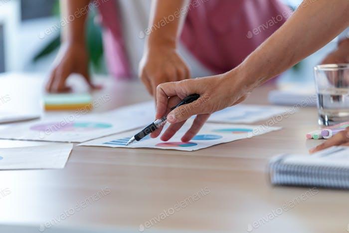 Die Hände von Geschäftsleuten, die auf die Statistiken des Unternehmens im Büro zeigen.