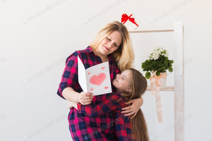 Child daughter congratulates mom and gives her postcard.
