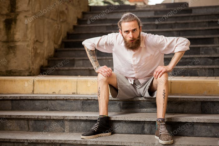 Tattoed and bearded hipster guy posing outdoor