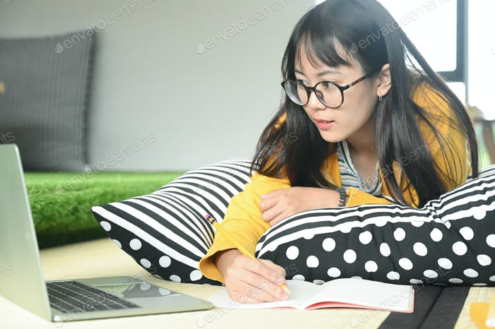 Teenage female student sleep on pillows read book and use laptop.