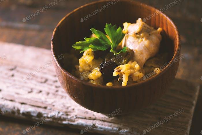 Pilaf mit Reis, Huhn und Rosinen in einer Holzschüssel Seitenansicht