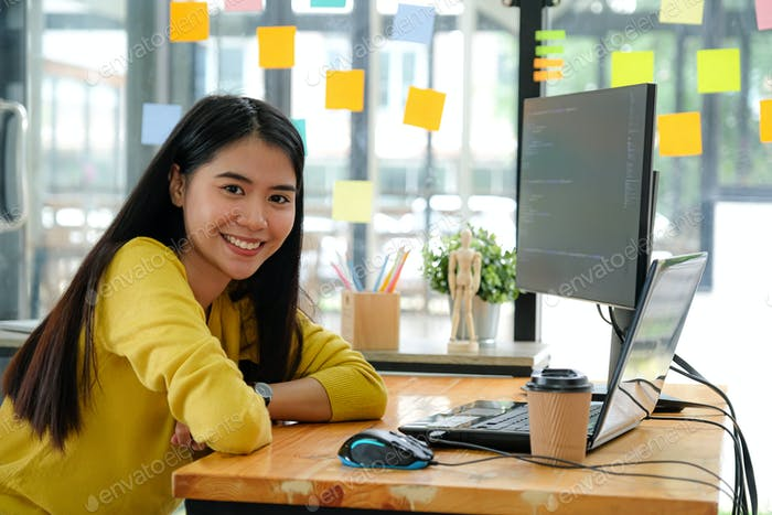 Asian female programmer sat at her desk at the office. She looked and smiled happily.