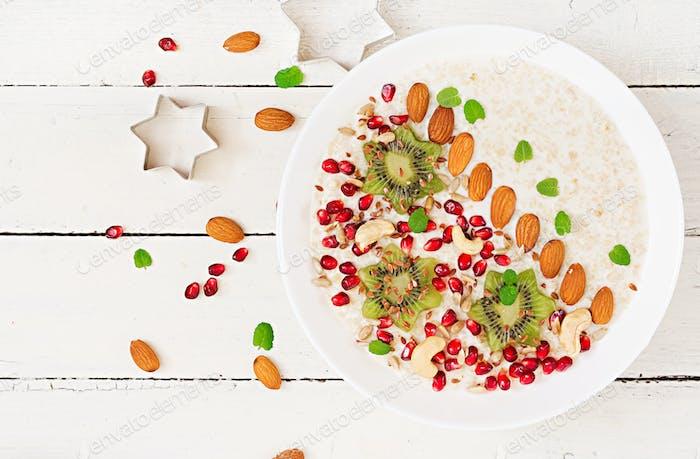 Tasty and healthy oatmeal porridge with kiwi, pomegranate and seeds