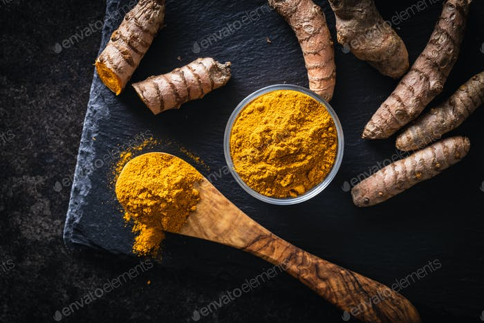 Indian turmeric powder and root. Turmeric spice. Ground turmeric.