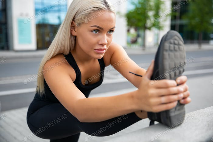 Entschlossene Frau tun Stretching Übung am Bürgersteig Geländer