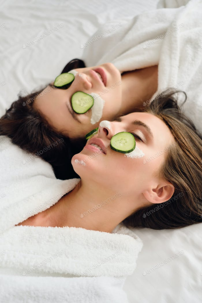 Sensual women in bathrobes with cosmetic mask and slices of cucumber on faces dreamily lying in bed