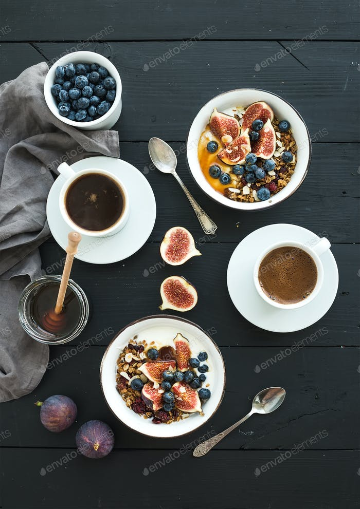 Healthy breakfast set. Bowls of oat granola with yogurt, fresh blueberries and figs
