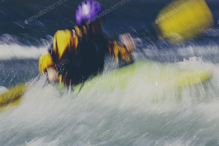 Long exposure of female whitewater kayaker paddling rapids and surf on a fast flowing river.