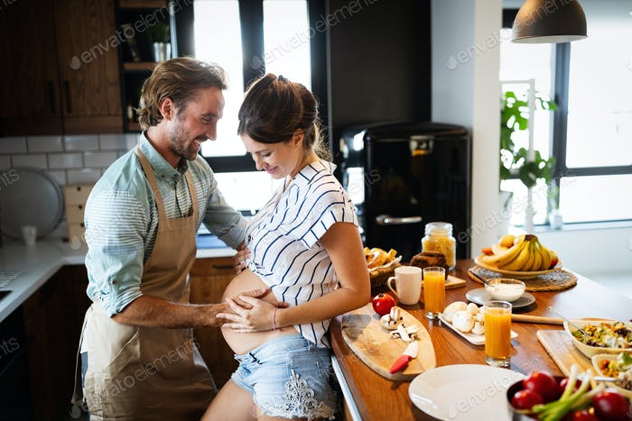 Glückliches Paar Kochen zusammen in der Küche, während Mann berühren Bauch seiner schwangeren Frau