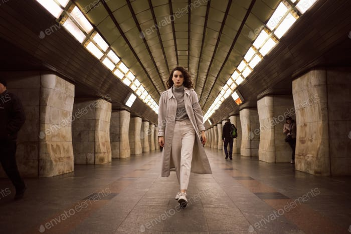 Attractive girl in trench coat confidently walking through subway station
