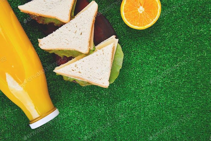 Picknick auf dem Gras. gesundes Essen Sandwich und Obst, Orangensaft