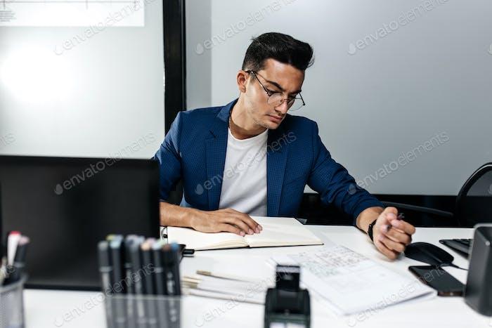 Der Architekt in einer dunkelblauen Jacke gekleidet arbeitet mit Dokumenten auf dem Desktop im Büro