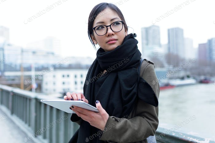 Beautiful asian young woman using her digital tablet in front of