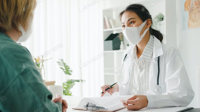 Young lady doctor wear mask delivering great news talk discuss result with patient in hospital.
