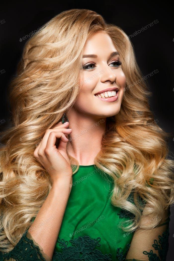 Портрет элегантной сексуальной блондинки женщины с длинными вьющимися волосами и гламурным макияжем.