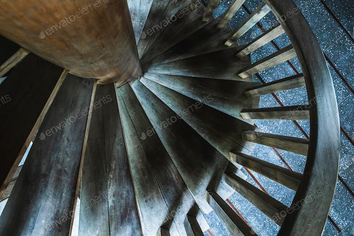 Detail of wooden spiral staircase, abstract geometric wallpaper in dark tones. Round stairs.