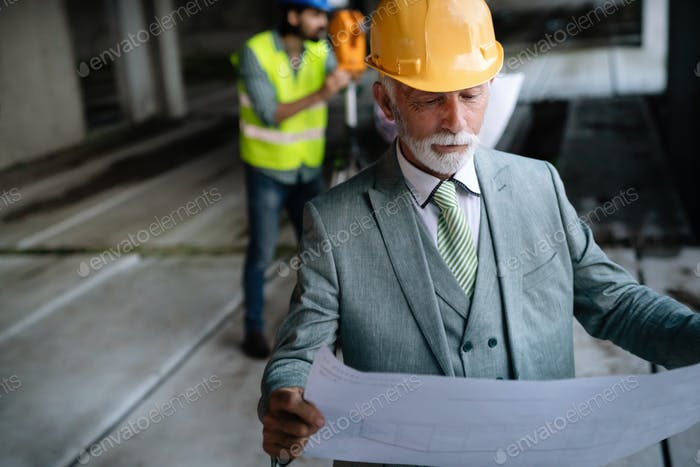 Confident construction engineer, architect, businessman in hardhat working on building site