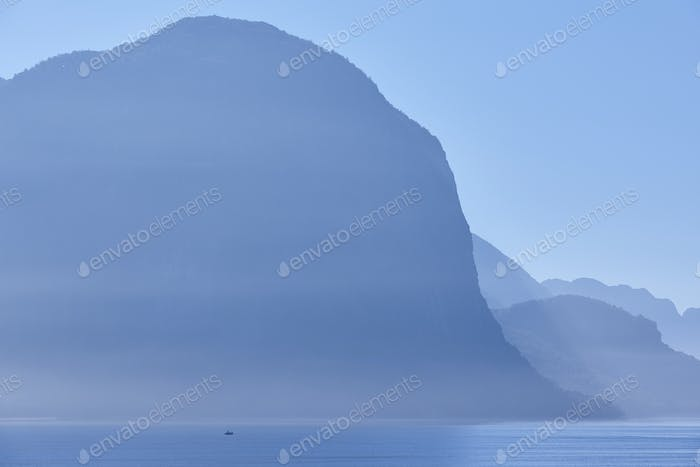 Norwegian fjord landscape sunrise in blue tone. Fisherman solitude. Horizontal