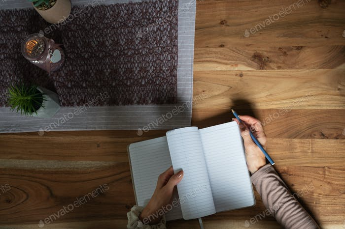 Top view of female hands opening blank notepad to write in it