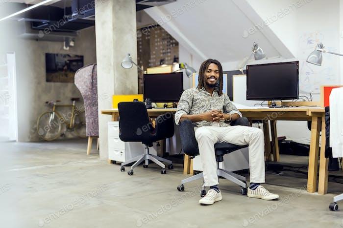 Handsome graphics designer sitting at a desk