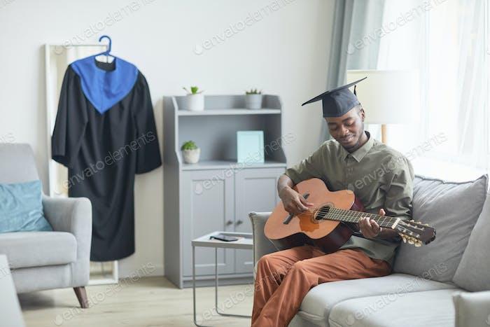 School graduate playing guitar